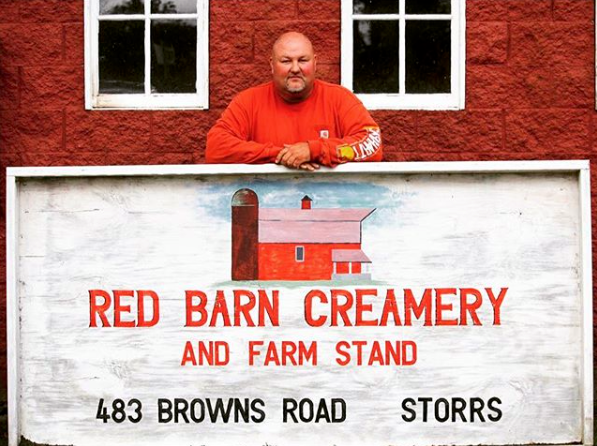 Farmer standing next to sign for Stearns Farm Stand